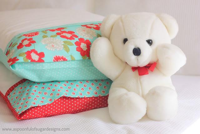 white teddy bear next to two pillows